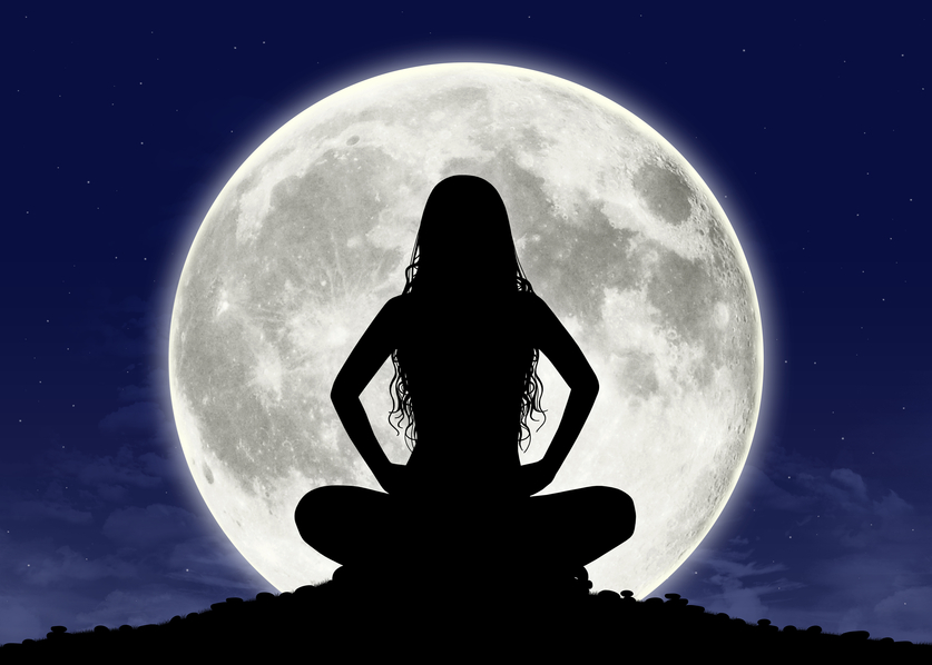 silhouette of a young beautiful woman with long hair in meditation posture with the full moon on the background
